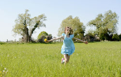 Girl running on meadow Royalty Free Stock Photos