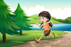A girl running near the riverbank with pine trees Royalty Free Stock Photos