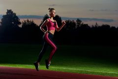 Girl running at night on stadium preparing for marathon. Side view of pretty and athletic girl in stylish black and pink sport wear running at night on stadium royalty free stock images