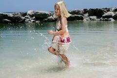 Girl running through ocean. Carefree young girl running through ocean Royalty Free Stock Photography