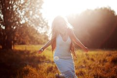 Girl is running out. Young woman in field, feel freedom and happiness. Casual style. Stock Photography
