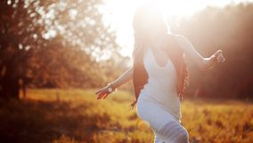 Girl is running out. Young woman in field, feel freedom and happiness. Casual style. Face in sunlight Royalty Free Stock Photo