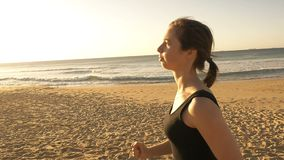 Girl running outdoors jogging to increase fitness through exercise slow motion. Clip of a sporty girl woman jogging isolated who is running outdoors in the stock video footage