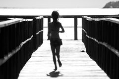 Girl running on pier. Abstract silhouette of a young girl running to the end of a pier Royalty Free Stock Images