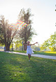 Girl running with rainbow kite. Mixed race  - african and caucasian. Summer day in park. Royalty Free Stock Photos
