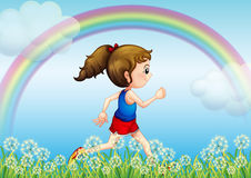 A girl running with a rainbow in the sky Royalty Free Stock Photo