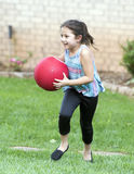 Girl running with red ball. An eight year old Amerasian girl is running in short green grass carrying a red ball in her hands.  She has a big smile.  She has Royalty Free Stock Photo