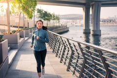 Girl running by the river in a urban city environment royalty free stock photography