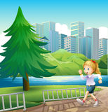 A girl running at the riverbank with a tall pine tree Stock Photo