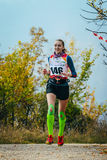 Girl running on road in autumn forest in compression socks and kinesio tape on knees royalty free stock images