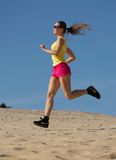 Girl running on sand Stock Image