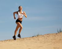 Girl running on sand Stock Photography