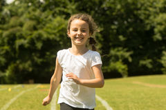 Girl running at School Sports Day. Young child sprinting hard and happily during summer traditional school event Royalty Free Stock Image