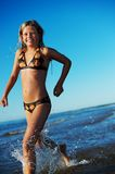 Girl running in the sea Stock Images