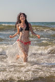 Girl running in sea surf Stock Photo