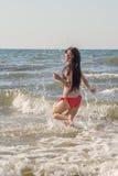 Girl running in sea surf Stock Photos