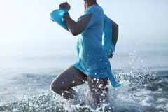 Girl running in the sea water Stock Images