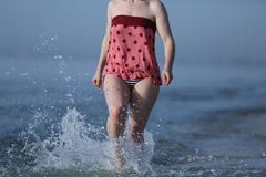 Girl running in the sea water Royalty Free Stock Image
