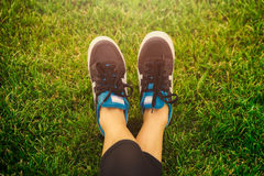 Girl running shoes closeup, green grass, woman fitness Royalty Free Stock Image