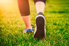 Girl running shoes closeup, green grass, woman fitness Royalty Free Stock Photos