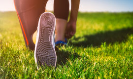 Girl running shoes closeup, green grass, woman fitness Stock Images
