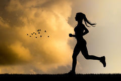 Girl running silhouette at sunset Stock Photography