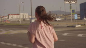 The girl is running. Slow motion. A young girl jogging in the early morning. stock footage