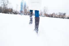 Girl running in the snow, late. Feet close-up royalty free stock images