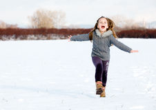 Girl running on snow in park Stock Image