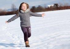 Girl running on snow in park Stock Photo