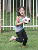 Girl running with a soccer ball Stock Photo