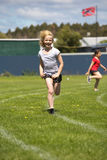 Girl running in sports race. Royalty Free Stock Photography