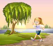 A girl running at the street with a giant tree Stock Photography