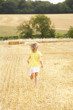 Girl Running Through Summer Harvested Field Royalty Free Stock Photography