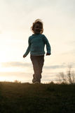 Girl running at sunset Stock Image