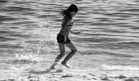 Girl running in surf Stock Photos