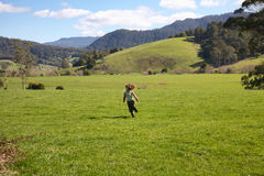 Girl running in Tasmanian farmland Royalty Free Stock Images