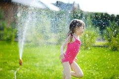 Girl running though a sprinkler Stock Image