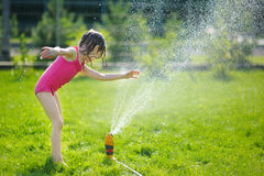 Girl running though a sprinkler Royalty Free Stock Images