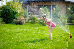 Girl running though a sprinkler Stock Photography