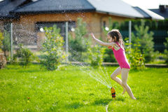Girl running though a sprinkler Royalty Free Stock Photography