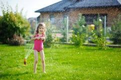 Girl running though a sprinkler Stock Photos