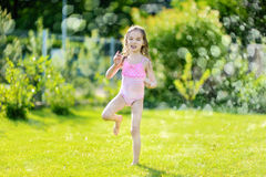 Girl running though a sprinkler in a backyard Royalty Free Stock Photos