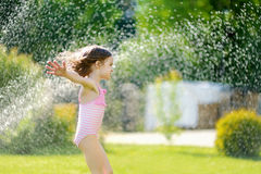 Girl running though a sprinkler in a backyard Royalty Free Stock Images