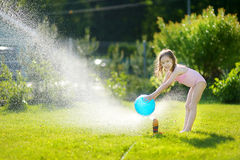 Girl running though a sprinkler in a backyard Stock Image