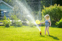 Girl running though a sprinkler in a backyard Royalty Free Stock Image