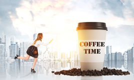 Girl running to a giant paper cup of coffee Stock Photos