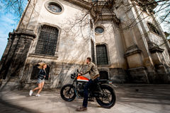 Girl running to her boyfriend sitting on the motorcycle in the old city, general plan Royalty Free Stock Photos