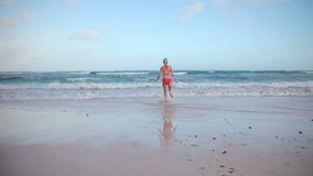 Girl Running to the Sea. And Jumping in the Water stock footage