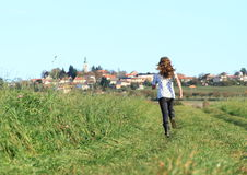 Girl running to village Stock Photo